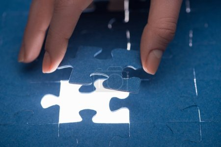 Photo for Cropped image of businesswoman inserting last missing puzzle, business concept - Royalty Free Image