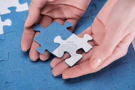 Photo for Cropped image of businesswoman assembling blue and white puzzles together, business concept - Royalty Free Image