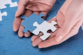 cropped image of businesswoman assembling blue and white puzzles together, business concept
