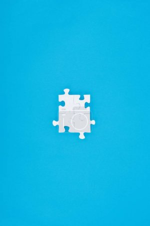 top view of assembled white puzzles isolated on blue, business concept