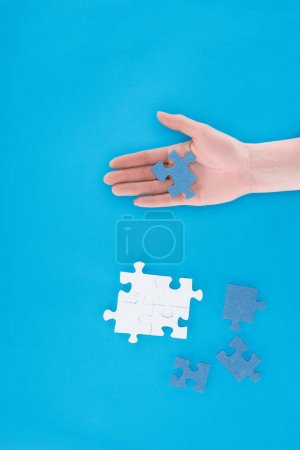 cropped image of businesswoman assembling puzzles and holding one piece on hand isolated on blue, business concept