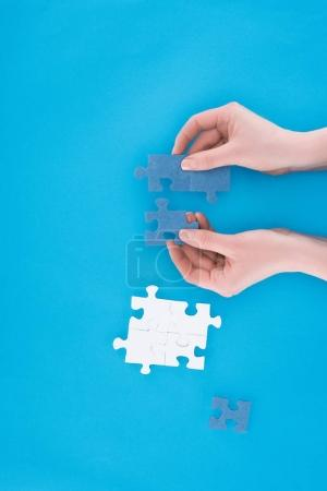 cropped image of businesswoman assembling blue puzzles isolated on blue, business concept