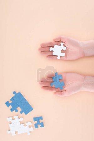 image recadrée de femme d'affaires détenant puzzles bleus et blancs en mains isolés sur beige, concept d'entreprise
