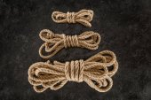 top view of arrangement of tied brown marine ropes on dark concrete surface