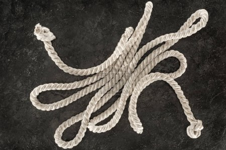 top view of white nautical rope with knots on dark concrete tabletop