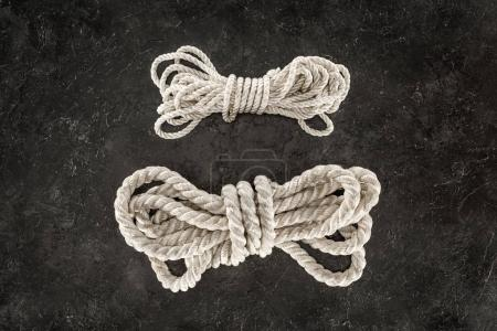 top view of arranged tied white marine ropes on dark concrete tabletop