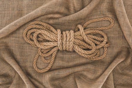 top view of arranged tied brown nautical rope on sackcloth
