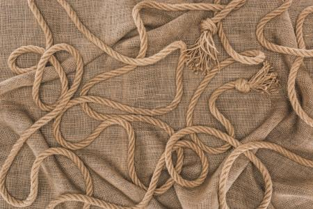top view of arranged brown nautical rope with knots on sackcloth
