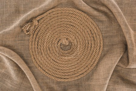 top view of brown nautical rope arranged in circle on sackcloth