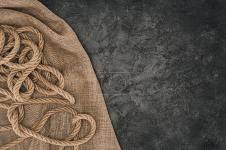 top view of arranged brown nautical rope on sackcloth on dark concrete surface