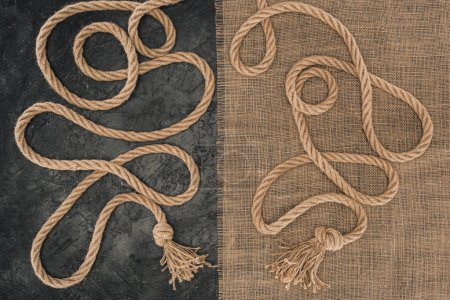 flat lay with brown marine ropes with knots on sackcloth and dark concrete surface
