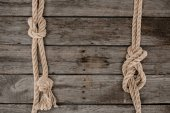 flat lay with marine ropes with knots on grunge wooden tabletop