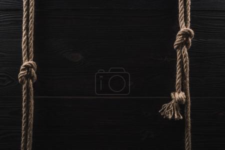 Photo pour Vue de dessus de la disposition des cordes nautiques brunes avec nœuds sur plateau en bois foncé - image libre de droit