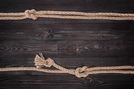 top view of arrangement of brown nautical ropes with knots on dark wooden tabletop