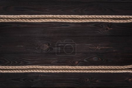 top view of arrangement of brown nautical ropes on dark wooden tabletop