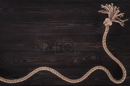 top view of brown nautical rope with knot on dark wooden surface