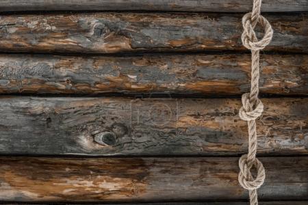 Draufsicht auf nautisches Seil mit Knoten auf Grunge-Holzoberfläche