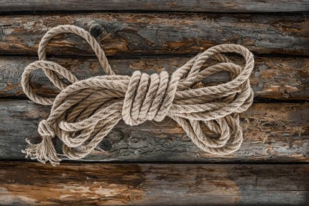 top view of tied nautical rope on grunge wooden surface