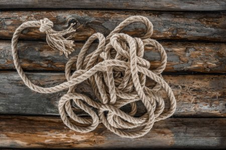 top view of nautical rope with knot on grunge wooden surface