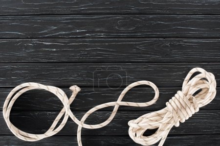 top view of tied white marine rope on dark wooden tabletop