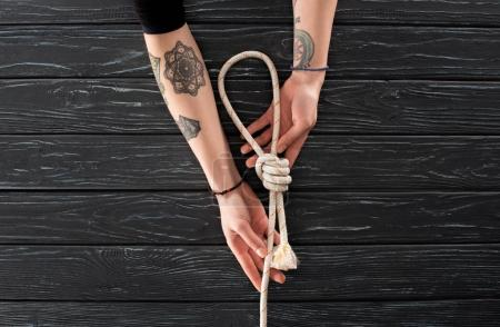 partial view of female tattooed hands with nautical rope with knot on dark wooden surface
