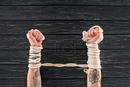 cropped shot of female tattooed hands tied in rope on dark wooden tabletop