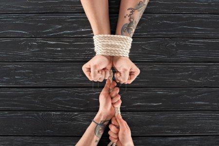 Photo pour Vue partielle de la femme attachant la corde autour des mains masculines sur la surface en bois sombre - image libre de droit