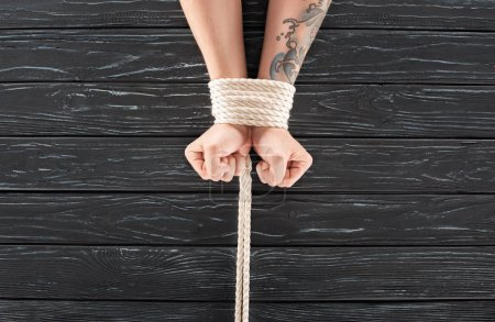 cropped shot of male hands tied with marine rope on dark wooden surface