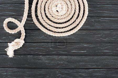 top view of white marine rope arranged in circle on dark wooden tabletop