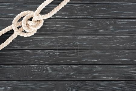 top view of white nautical rope with knot on dark wooden surface