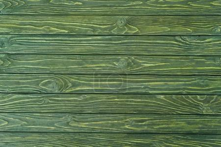 Wooden horizontal planks painted in green background