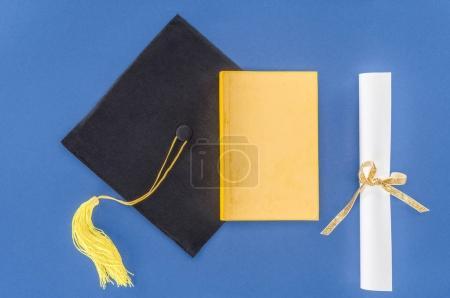 Sombrero de graduación con diploma y libro aislado en azul