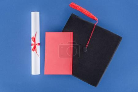 Education concept with diploma and graduation cap isolated on blue