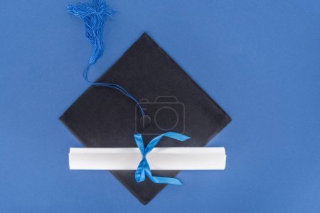 Graduation hat and diploma with blue ribbon isolated on blue