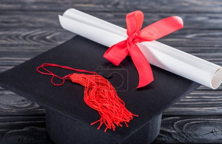 Graduation hat and diploma with red ribbon on wooden table