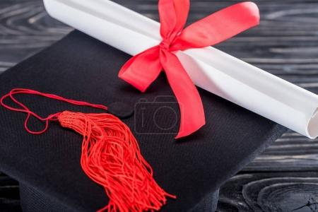 Education concept with diploma and graduation cap on wooden table