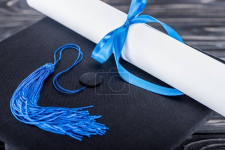 Photo for High school concept with diploma and graduation cap on wooden table - Royalty Free Image