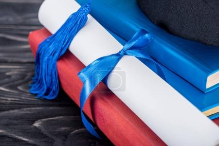 Graduation hat and diploma with blue ribbon on stack of books