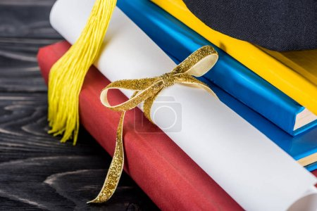 Graduation hat and diploma with yellow ribbon  on stack of books
