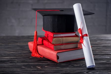 Graduation cap with diploma and books on table