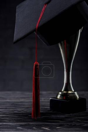 Trophy cup with graduation cup on wooden table