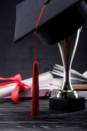 Trophy cup with graduation cup in front of books and diploma