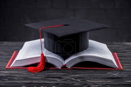 Open book with graduation cap on wooden table