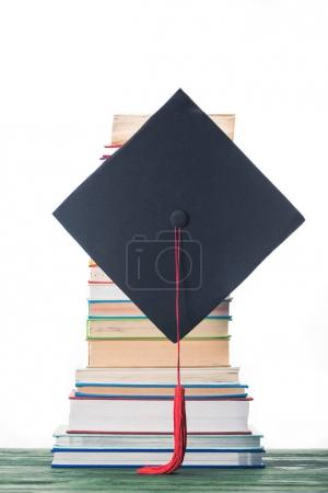 Graduation cap in front of stacked books