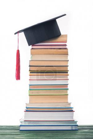 Graduation concept with stacked books and graduation hat