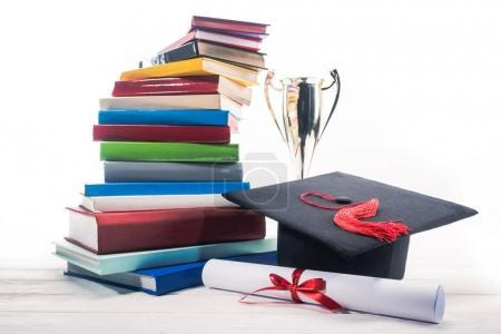 Graduation hat with diploma and trophy cup by stack of books