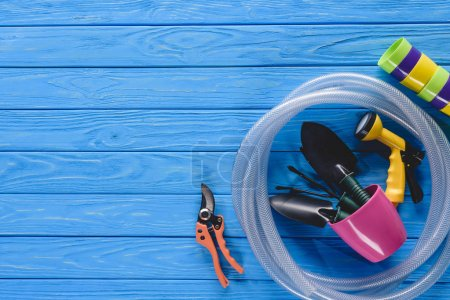 top view of flower pots, hose and gardening tools on blue wooden planks
