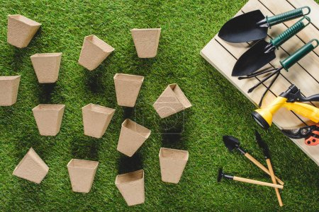 top view of gardening equipment and pile of flower pots on grass