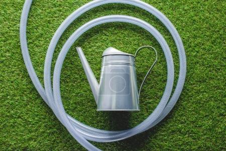 top view of watering can surrounded by hose on grass