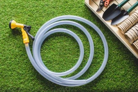 Photo for Top view of hosepipe and gardening equipment on planks - Royalty Free Image